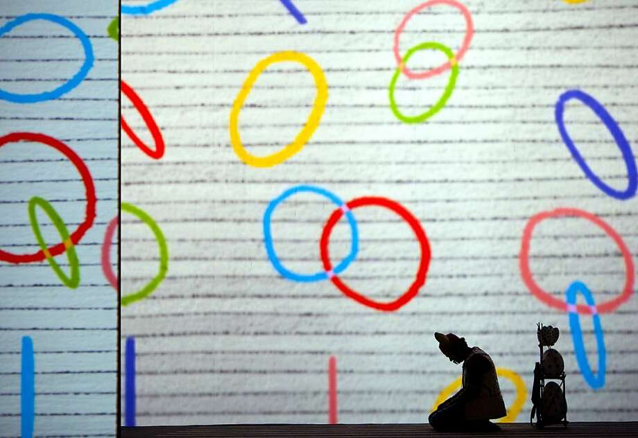 """Papageno (Nathan Gunn), is silhouetted by the projected animated screen during a production of """"The Magic Flute"""". The San Francisco Opera presents a new production Mozart's """"The Magic Flute,"""" which features over-the-top characters and projected animated sets. Photo: Kevin Johnson, The Chronicle"""