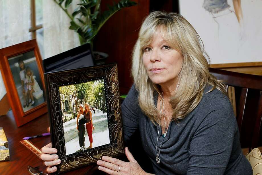Cally Houck holds a picture in February of her daughters who were killed in 2004 in a rental car that was under recall. Photo: Joe Kohen, AP IMAGES FOR CHANGE.ORG