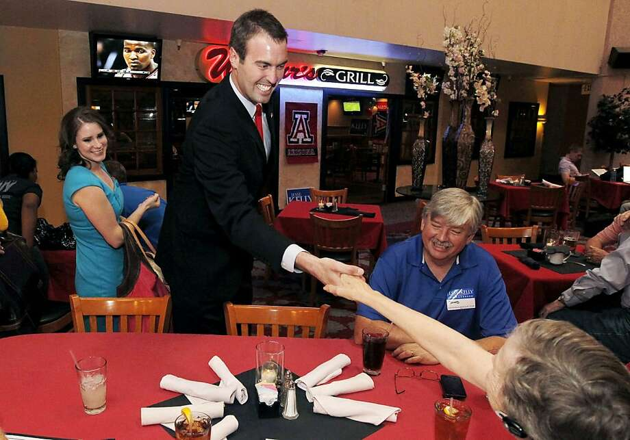 Jesse Kelly, R-Ariz., smiles and shakes hands with supporters as he arrives for a post-election night event Tuesday, June 12, 2012, in Tucson, Ariz. Kelly is running against Democrat Ron Barber, Gabrielle Giffords' former district director, for the seat Giffords left in January to focus on her recovery from a gunshot wound to her head during a gunman's shooting spree a year earlier. (AP Photo/Ross D. Franklin) Photo: Ross D. Franklin, Associated Press