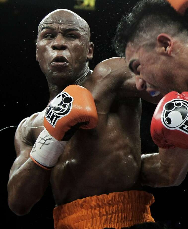 FILE - This Sept. 17, 2011 file photo shows Floyd Mayweather Jr., left, punching Victor Ortiz during their WBC welterweight title fight in Las Vegas. Lawyers for Mayweather say the undefeated champion boxer may never fight again if he's not released from the Las Vegas jail he entered earlier this month. (AP Photo/Julie Jacobson, File) Photo: Julie Jacobson, Associated Press