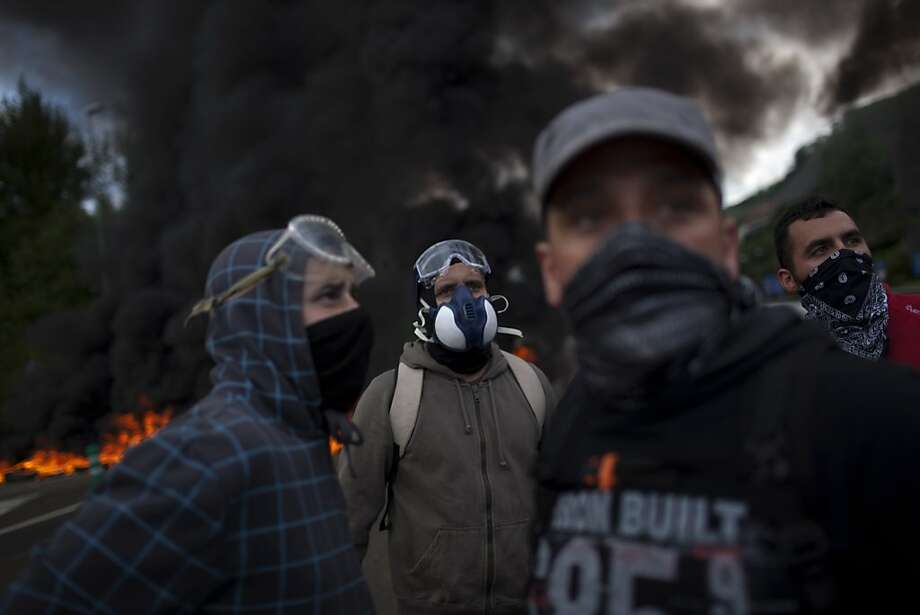 Undercover miners are seen next to burning tires as they block a motorway in Campomanes, Oviedo, Spain, Tuesday, June 12, 2012. Strikes, road blockades, and mine sit-ins continue as 8,000 mineworkers at over 40 coal mines in northern Spain continue their protests against government action to cut coal subsidies. (AP Photo/Emilio Morenatti) Photo: Emilio Morenatti, Associated Press