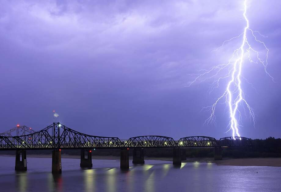 A bolt of lighting lights up the night sky over the Mississippi River bridges at about 9:30 p.m. Monday night, June 11, 2012 in Vicksburg, Miss. Severe storms that moved through Mississippi Monday night left downed trees and power outages in its wake. (AP Photo/The Vicksburg Evening Post, Brenden Neville) Photo: Brenden Neville, Associated Press