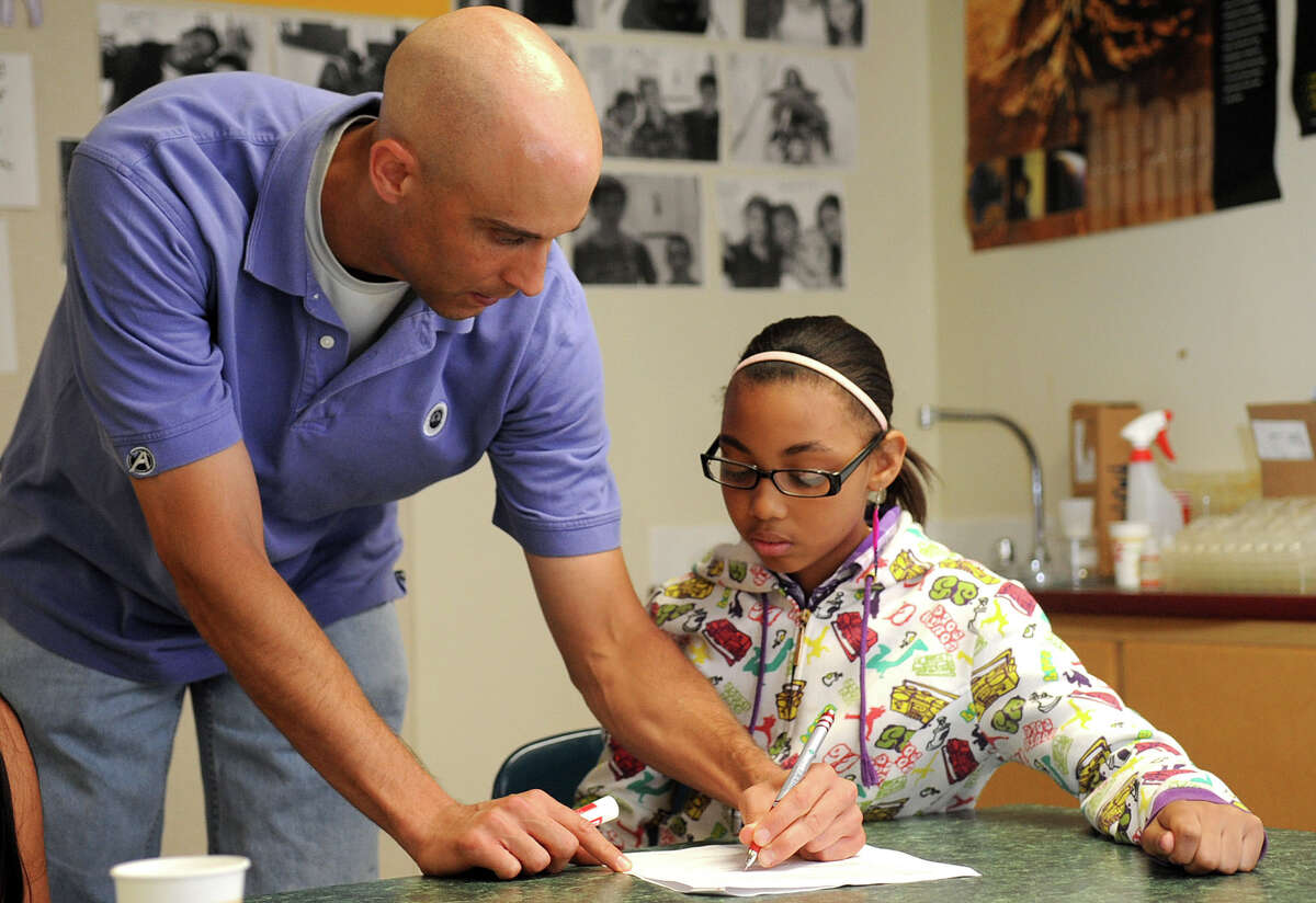 Brian Butera helps Amaiya Callahan during final review in his 6th grade science class at Turn of River Middle School on Wednesday, June 13, 2012. He and his students participated in a NASA data collection project about clouds.