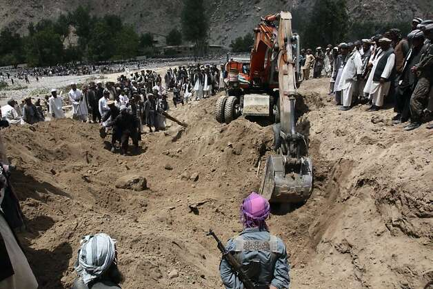 A crane is used to search for victims of Monday's earthquake in Baghlan, north of Kabul, Afghanistan on Tuesday, June 12, 2012. Scores of people are feared entombed under tons of rock and stone that buried a village in a landslide after two earthquakes in northern Afghanistan, authorities said Tuesday. A single bulldozer worked to uncover the bodies of those killed in Monday's landslide after the earthquakes struck the Hindu Kush region, but villagers fear there will be no survivors. (AP Photo/Jawed Dehsabzi) Photo: Jawed Dehsabzi, Associated Press
