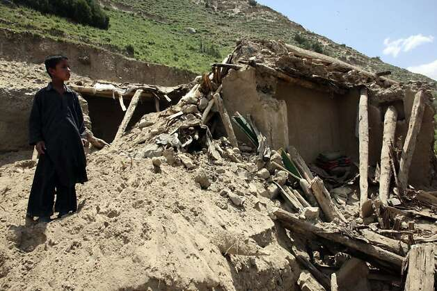 A boy stands by the ruins of a home after Monday's earthquake in Baghlan, north of Kabul, Afghanistan on Tuesday, June 12, 2012. Scores of people are feared entombed under tons of rock and stone that buried a village in a landslide after two earthquakes in northern Afghanistan, authorities said Tuesday. A single bulldozer worked to uncover the bodies of those killed in Monday's landslide after the earthquakes struck the Hindu Kush region, but villagers fear there will be no survivors.  (AP Photo/Jawed Dehsabzi) Photo: Jawed Dehsabzi, Associated Press