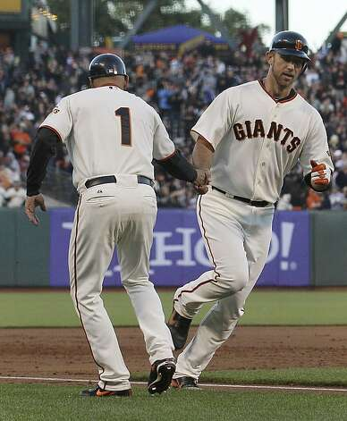 San Francisco Giants pitcher Madison Bumgarner, right, is congratulated by third base coach Tim Flannery after hitting a solo home run off of Houston Astros pitcher Bud Norris during the third inning of a baseball game in San Francisco, Tuesday, June 12, 2012. (AP Photo/Jeff Chiu) Photo: Jeff Chiu, Associated Press