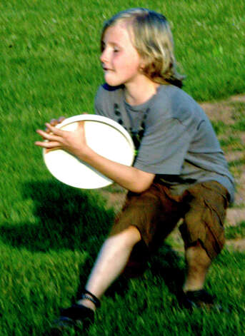 "Max Cook, 11, of Kent makes a fine catch as he plays Frisbee with his father, Otis Cook, and friend Alyssa Cassidy of Sherman during the Village Center for the Arts' inaugural ""Paint the People"" art festival at Young's Field in New Milford. June 9, 2012 Photo: Norm Cummings"