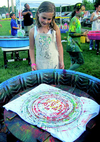 "Annabelle Colonna, 8, of New Milford appears pleased with her own ""spin art"" T-shirt design during the Village Center for the Arts' inaugural ""Paint the People"" art festival  in New Milford. June 9, 2012 Photo: Norm Cummings"