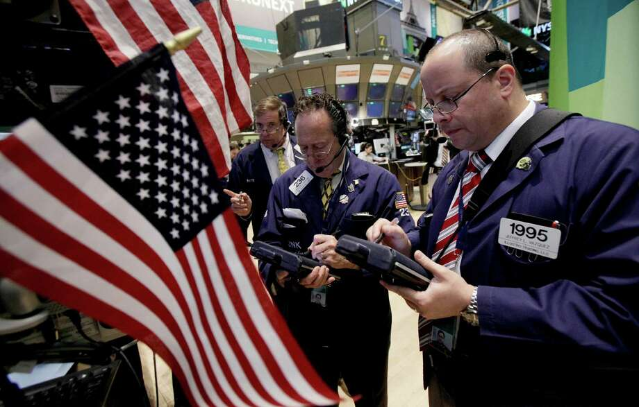 FILE- In this Monday, June 11, 2012, file photo, traders Stephen Kaplan, center, and Jeffrey Vazquez, right, work on the floor of the New York Stock Exchange. U.S. stocks were poised to fall Wednesday June 13, 2012. Dow futures lost 0.1 percent to 12,500.00 while broader S&P 500 futures dropped 0.2 percent to 1,317.70.  (AP Photo/Richard Drew, FIle) Photo: Richard Drew / AP