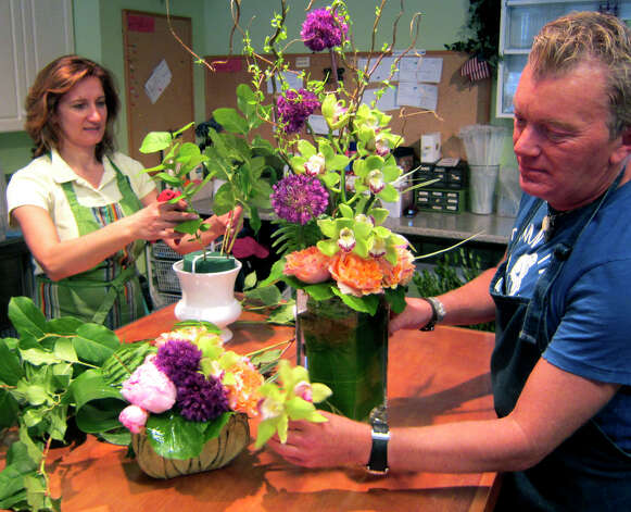 Floral designer Craig Hapler is shown creating an arrangement for a wedding at Ruth Chase Flowers, assisted by shop owner Luisa Amaral. Nicole Everett also designs arrangements at the New Milford business. June 2012 Photo: Norm Cummings