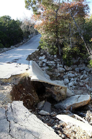 BIZ –A damaged bridge is seen on a road in the Clearwater Ranch subdivision in Northwest Bexar County, Wednesday, Nov. 30, 2011. The bridge washed out during the 2007 floods. Lots in the 11-acre plus range were sold by a developer that stopped work after selling many of the expensive home sites in the over 300-acres development. Now the owners of the lots are struggling to get CPS service and septic permits, and are dealing with a variety of bureaucratic issues such as golden checked warbler studies, an unauthorized low-water crossing, FEMA and U.S. Fish and Wildlife JERRY LARA/glara@express-news.net Photo: JERRY LARA, San Antonio Express-News / SAN ANTONIO EXPRESS-NEWS
