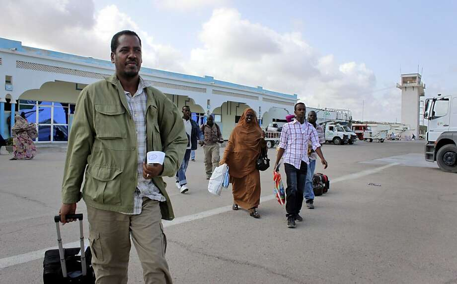 In this photo taken Friday, June 8, 2012, Abdikhafar Abubakar prepares to board a plane back to Minneapolis after returning to Mogadishu to visit his mother for the first time in decades, at the airport in Mogadishu, Somalia. The seaside Somali capital is enjoying a peace that, except for the infrequent attack, has lasted the better part of a year and Somalis who fled decades of war are coming back, as are U.N. workers who long operated out of Nairobi, the capital of neighboring Kenya. (AP Photo/Jason Straziuso) Photo: Jason Straziuso, Associated Press