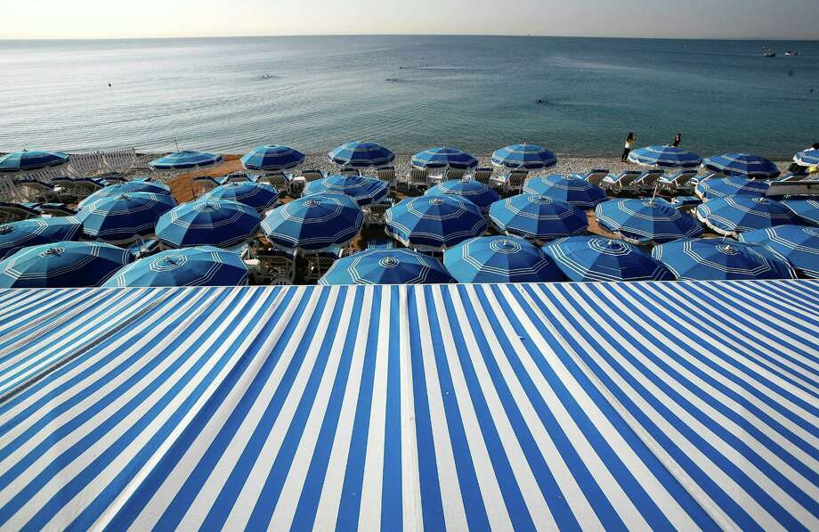 FILE - In this file photo taken Sept. 27, 2011, people swim in the Mediterranean Sea as blue beach umbrellas provide shade from the sun along the beach in Nice, southeastern France. The city of Nice attracts tourists year-round thanks to the flower market, restaurants, historic sites and events ranging from Mardi Gras to the annual film festival in Cannes. (AP Photo/Lionel Cironneau, File) Photo: Lionel Cironneau / AP