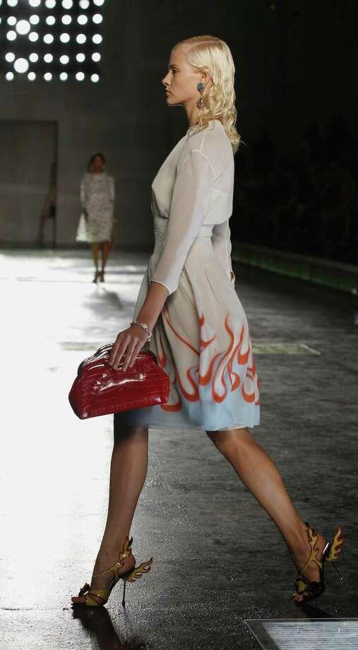 ACCESSORIZE: Fun heels and a bright-colored clutch add excitement to Prada?s runway look. Photo: Luca Bruno / AP