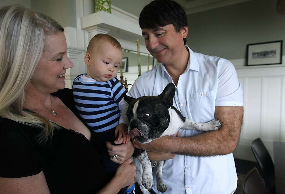 Bobbi Clemens and Mark Tacchi hold their 6-month-old son Leonardo and dog Napoleon at their home in San Francisco, Calif. on Wednesday, June 13, 2012. The family has tried unsuccessfully to win the city's lottery to convert their building from a tenancy-in-common to condos. Photo: Paul Chinn, The Chronicle