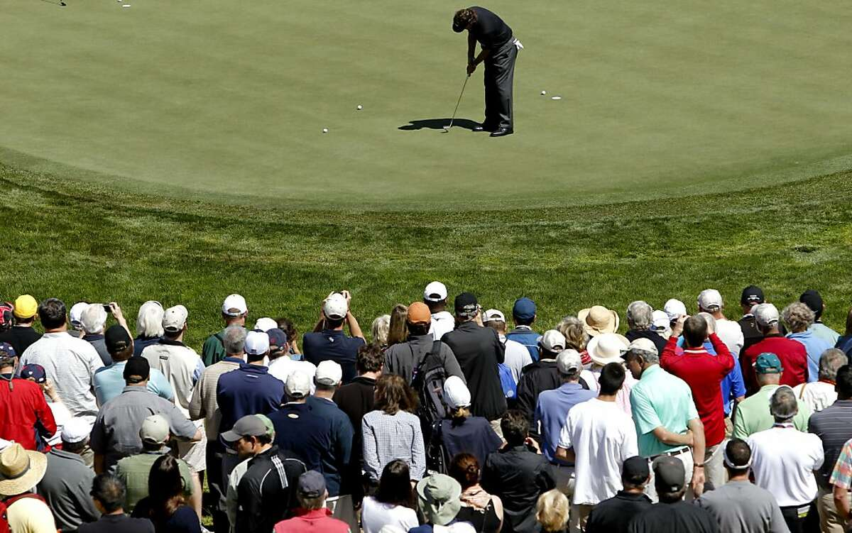 The gallery watches, as Phil Mickelson takes a few practice putts on the eighth green, as the second day of practice rounds continue during the United States Open Championship at the Olympic Club in San Francisco, Ca., on Tuesday June 12, 2012.