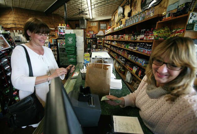 Phyllis Lippe, left of Southport, is waited on by cashier Pat Schroder at Spic & Span Market on Pequot Avenue in downtown Southport on Tuesday, June 5, 2012. Photo: Brian A. Pounds / Connecticut Post