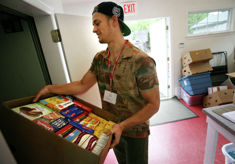 Karl Hueglin, of Wilton, moves boxes of food while volunteering at Person-to-Person in Darien on Tuesday, June 5, 2012. Person-to-Person utilises the website, volunteersquare.org, to find volunteers. Photo: Brian A. Pounds / Connecticut Post