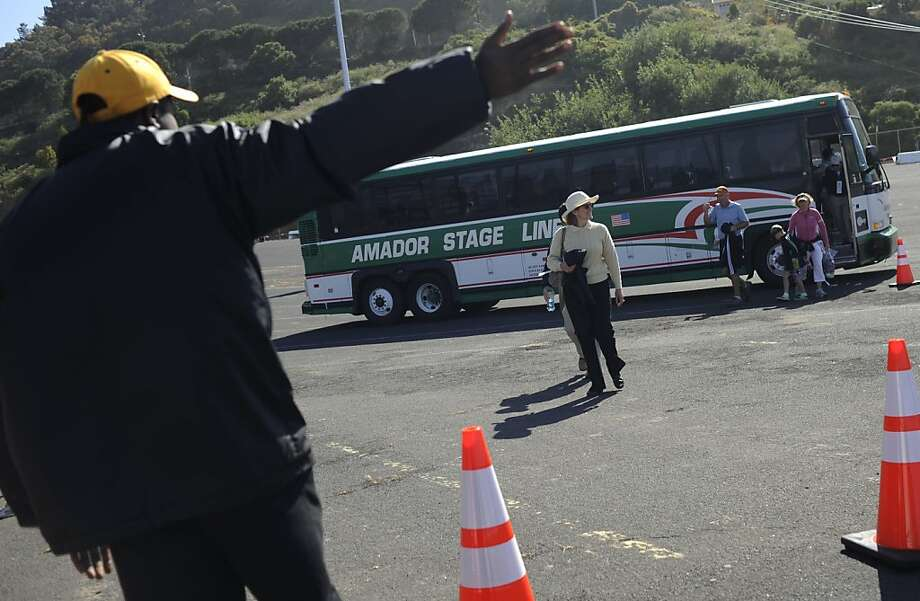 Deon Mark, right, security, points out the direction for the people who got back from the U.S. Open to The Candlestick Park back to their parking area on June 13, 2012, San Francisco, Calif. Photo: Yue Wu, The Chronicle