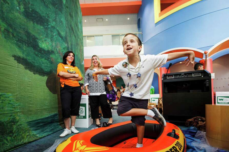 Peter Tsatsaronis, 9, plays a Kinect rafting game in a real raft as Amalia Gatlegos, left, and Miche