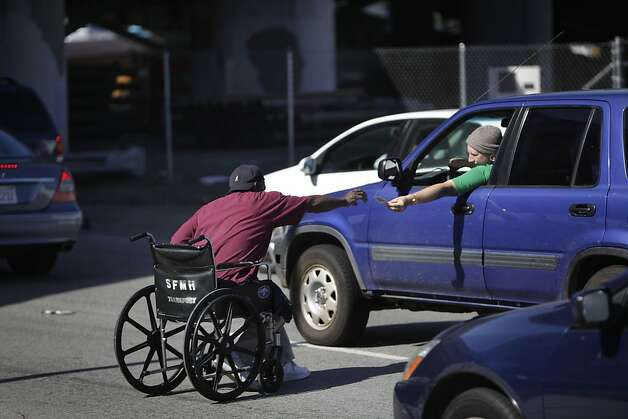 "Welcome Watson, who is homeless,  reaches for money handed to him by a driver as he panhandles on an I-80 on ramp at 5th and Bryant Streets as he sits in his wheelchair next to his dog Coco on Wednesday, June 13, 2012 in San Francisco, Calif. ""They know it's wrong,"" Watson explained about people who give to him, pointing to a Panhandling Prohibited sign posted on the corner, ""but people just want to help us out."" Photo: Lea Suzuki, The Chronicle"