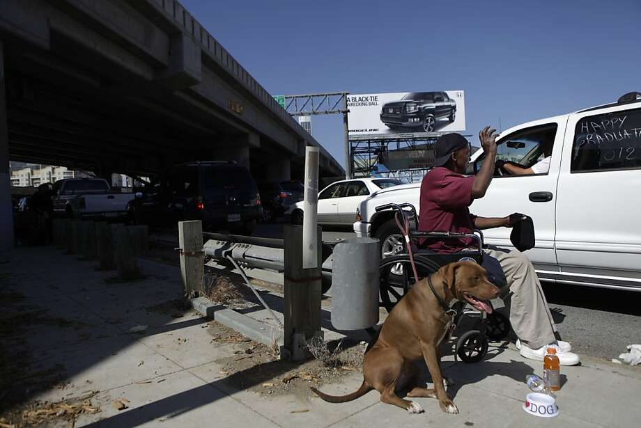 """Welcome Watson, who is homeless,  wishes the passengers of a passing car, """"Happy Graduation"""" as he panhandles on an I-80 on ramp at 5th and Bryant Streets as he sits in his wheelchair next to his dog Coco on Wednesday, June 13, 2012 in San Francisco, Calif. """"They know it's wrong,"""" Watson explained about people who give to him, pointing to a Panhandling Prohibited sign posted on the corner, """"but people just want to help us out."""" Photo: Lea Suzuki, The Chronicle"""