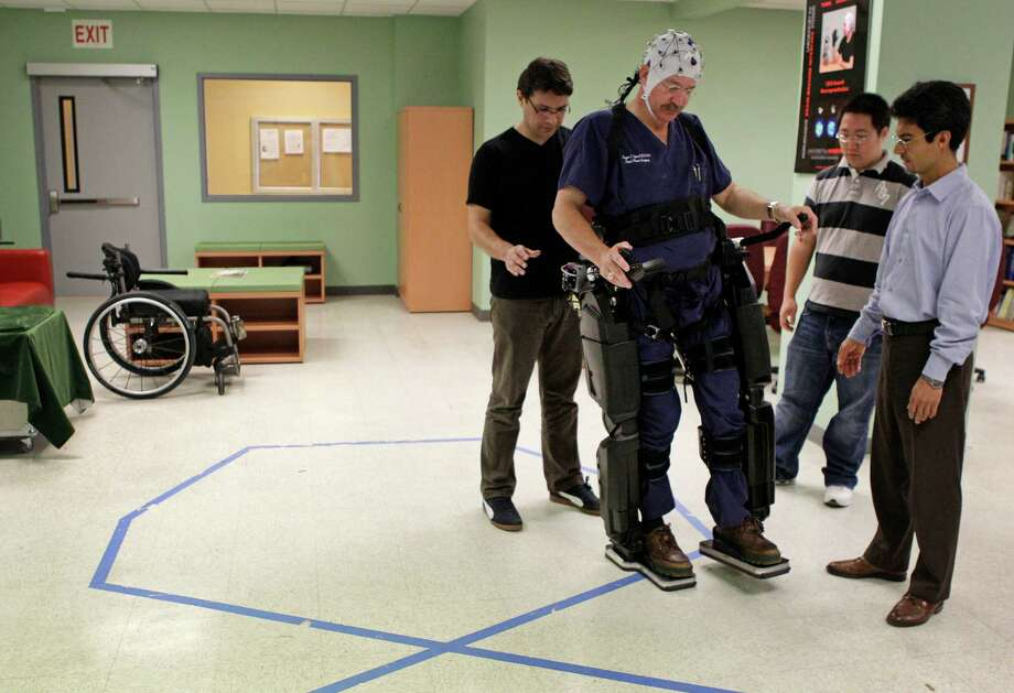 Dr. Eugene Alford, a paraplegic, tests a robotic exoskeleton at the University of Houston under the watchful eyes of research team members Atilla Kilicarslan, left, Andrew Paek, and professor Jose Luis Contreras-Vidal, right. Photo: Melissa Phillip / © 2012 Houston Chronicle