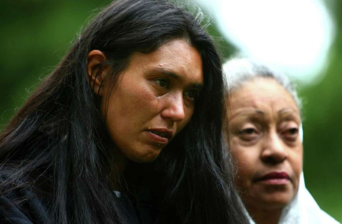 Christina Gomez, who said she knew a few of those buried from time on the streets, sheds a tear during a funeral for King County's homeless and indigent on Wednesday, June 13, 2012 at Mount Olivet Cemetery in Renton. The funeral for unclaimed bodies is held about every two years as part of King County's Indigent Remains Program. The Wednesday service honored the 154 people after their cremated remains were buried in a common plot.