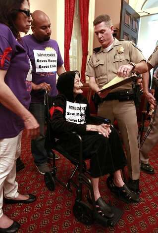 California Highway Patrol officer K. Kelly, right, explains the citation he has written for Maria Lopez, seated after she, her daughter Emma, left, and Paul Calderon, second from left, were detained during a protest against proposed state budget cuts to social services, at the Capitol in Sacramento, Calif., Wednesday June, 13, 2012.  More than 40 home care workers,  the disabled and supporters were arrested during a second day of protests against Gov. Jerry Brown's proposal to cut $225 million from the state's In-Home Supportive Services program, which provides care for the sick and disabled in their homes.(AP Photo/Rich Pedroncelli) Photo: Rich Pedroncelli, Associated Press