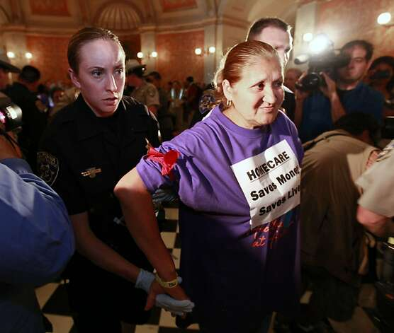 A demonstrator is removed from the rotunda of the state Capitol during a protest against proposed state budget cuts to social services in Sacramento, Calif., Wednesday June, 13, 2012.  More than 40 home care workers, disabled people and advocates were arrested during a second day of protests against Gov. Jerry Brown's proposal to cut $225 million from the state's In-Home Supportive Services program, which provides care for the sick and disabled in their homes.(AP Photo/Rich Pedroncelli) Photo: Rich Pedroncelli, Associated Press