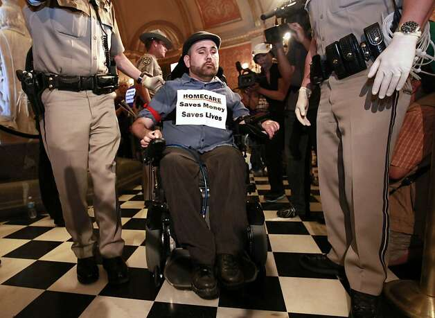 A wheelchair bound demonstrator is removed from the rotunda of the state Capitol during a protest against proposed state budget cuts to social services in Sacramento, Calif., Wednesday June, 13, 2012.  More than 40 home care workers, disabled people and advocates were arrested during a second day of protests against Gov. Jerry Brown's proposal to cut $225 million from the state's In-Home Supportive Services program, which provides care for the sick and disabled in their homes.(AP Photo/Rich Pedroncelli) Photo: Rich Pedroncelli, Associated Press