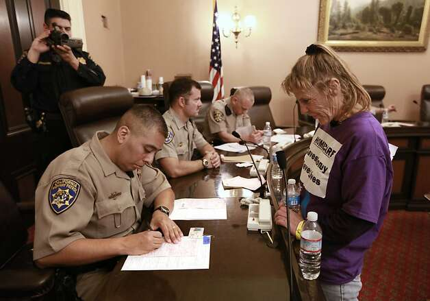 Lori Brown, an in-home health care worker from Whittier, watches  California Highway Patrol officer Pedro Delacruz  fill out the citation against her after she was detained during a protest against proposed state budget cuts to social services, at the Capitol in Sacramento, Calif., Wednesday June, 13, 2012.  More than 40 home care workers,  the disabled and supporters were arrested during a second day of protests against Gov. Jerry Brown's proposal to cut $225 million from the state's In-Home Supportive Services program, which provides care for the sick and disabled in their homes.(AP Photo/Rich Pedroncelli) Photo: Rich Pedroncelli, Associated Press