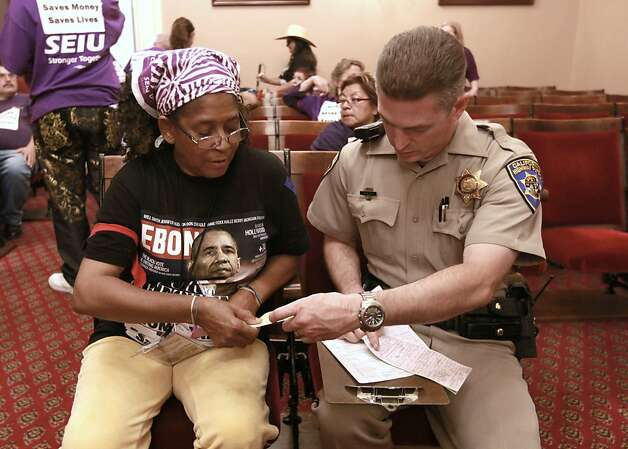 Lorine Calhoun, left, whose son receives in-home health care, is handed a citation from California Highway Patrol officer K. Kelly, after she was detained during a protest against proposed state budget cuts to social services, at the Capitol in Sacramento, Calif., Wednesday June, 13, 2012.  More than 40 home care workers,  the disabled and supporters were arrested during a second day of protests against Gov. Jerry Brown's proposal to cut $225 million from the state's In-Home Supportive Services program, which provides care for the sick and disabled in their homes.(AP Photo/Rich Pedroncelli) Photo: Rich Pedroncelli, Associated Press