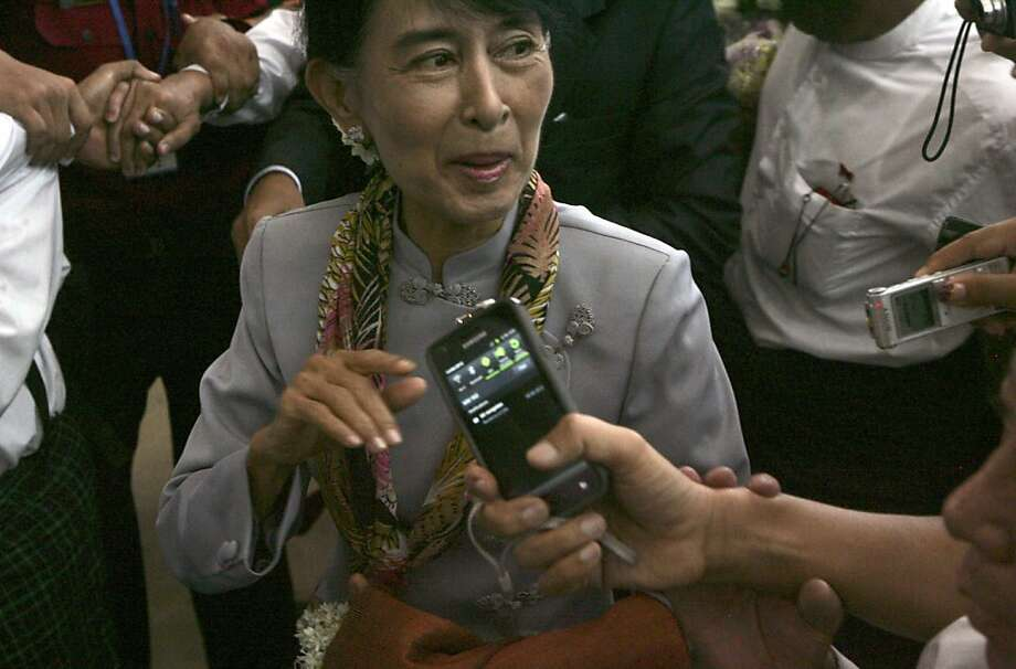 Myanmar opposition Leader Aung San Suu Kyi talks to reporters as she arrives at Yangon International airport Wednesday, June 13, 2012, in Yangon, Myanmar. Suu Kyi takes her first European trip since 1988 Wednesday to make a long-awaited acceptance speech for the 1991 Nobel Peace Prize and at a time when Myanmar is making tenuous democratic progress. (AP Photo/Khin Maung Win) Photo: Khin Maung Win, Associated Press