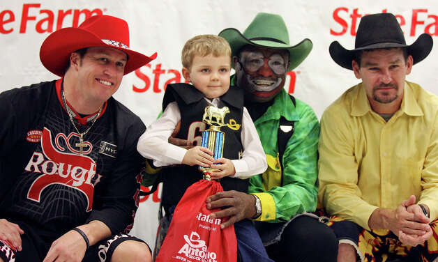 Mutton bustin' contestant Judge Trulove, 4, poses for photos with bullfighters Clay Collins (from left), Leon Coffee and Travis Adams after the event during the San Antonio Stock Show & Rodeo on Monday, Feb. 20, 2012, at the AT&T Center. Coffee is among the individuals responsible for looking out for the cowboys and the animals who enter and compete in the arena. Photo: Edward A. Ornelas, San Antonio Express-News / © SAN ANTONIO EXPRESS-NEWS (NFS)