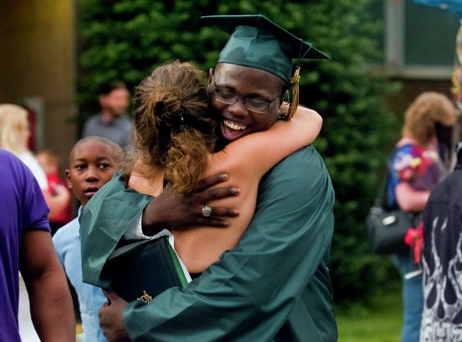 Graduate Cecil Bost, of Ansonia, hugs family friend Jeannie Crane, of Naugatuck, after Emmett O'Brien Technical High School's Class of 2012 Graduation Ceremony in Ansonia, Conn. on Wednesday June 13, 2012. Photo: Christian Abraham / Connecticut Post