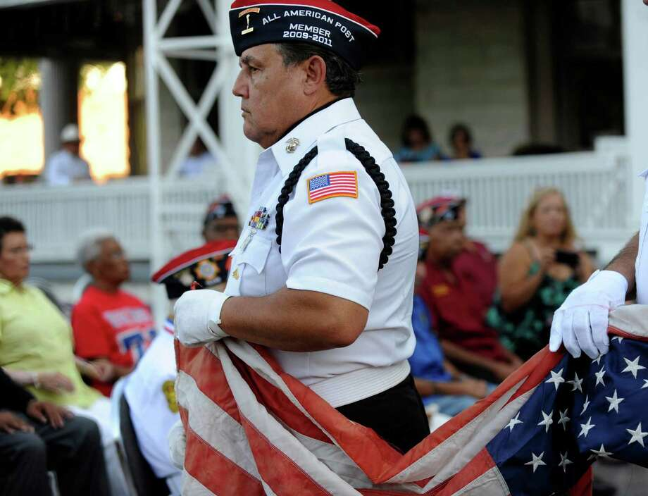 Jesse Alvarado carries a worn American flag to be disposed of during a flag retirement ceremony at VFW Post 76 on Wednesday, June 13, 2012. Photo: Billy Calzada, San Antonio Express-News / © 2012 San Antonio Express-News