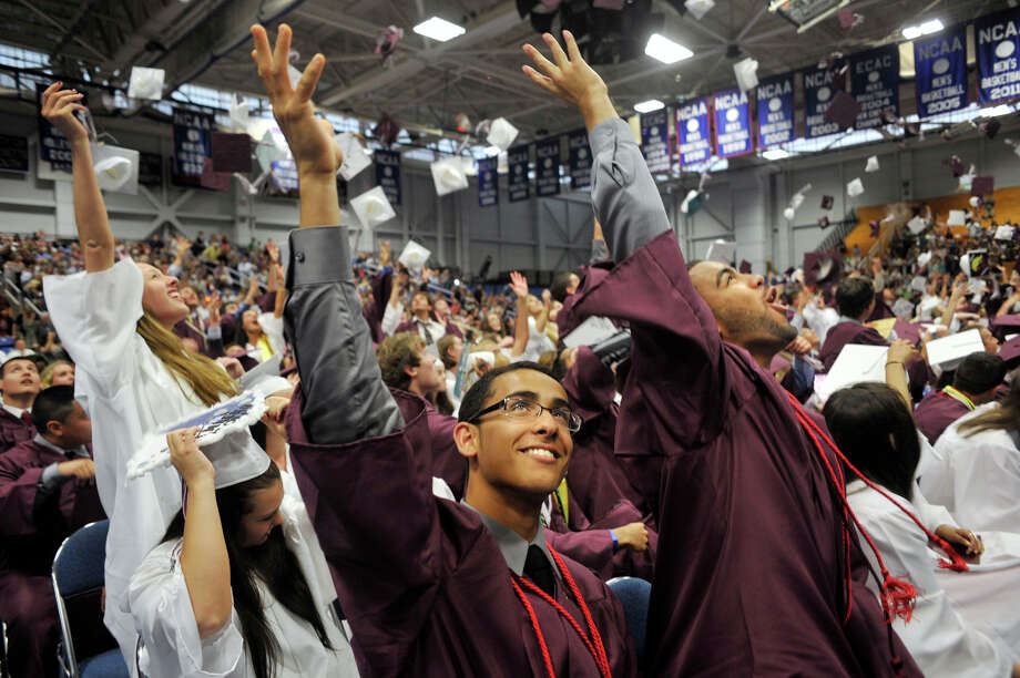 Davidson Abiali, center, throws his cap in the air during the Bethel High School graduation in the O'Neill Center at Western Connecticut State University's westside campus on Wednesday, June 13, 2012. Photo: Jason Rearick / The News-Times