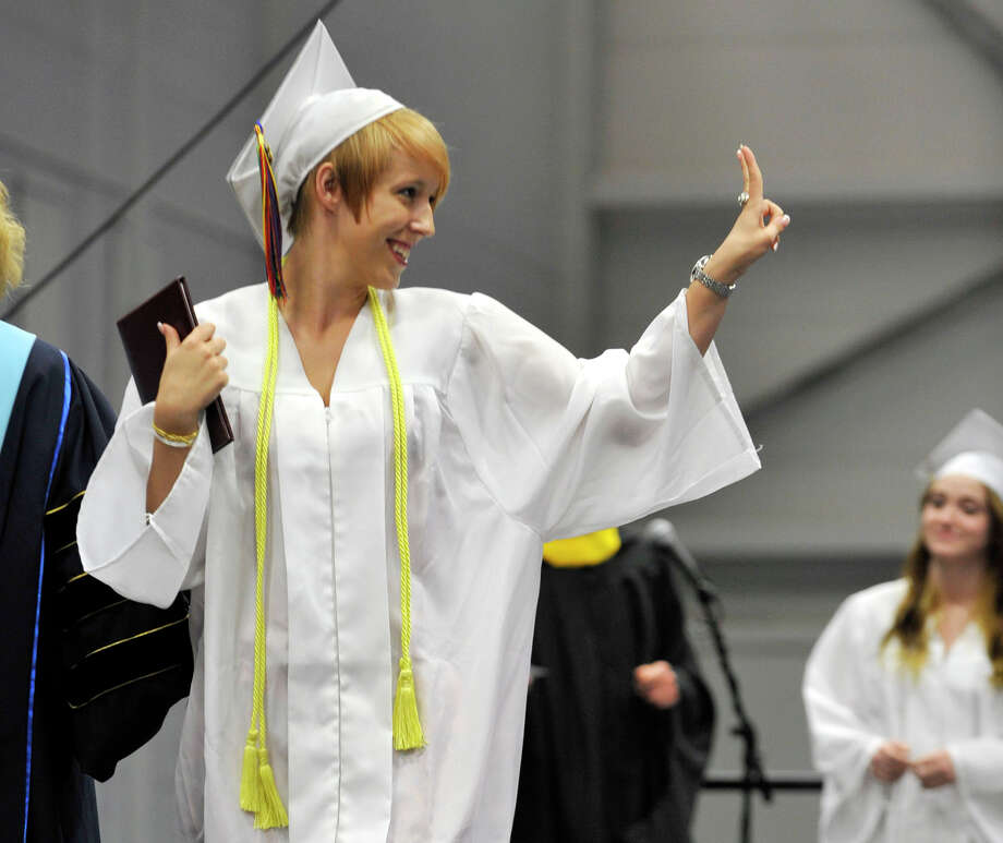 Anne Buchholz flashes the peace sign after accepting her diploma during the Bethel High School graduation in the O'Neill Center at Western Connecticut State University's westside campus on Wednesday, June 13, 2012. Photo: Jason Rearick / The News-Times