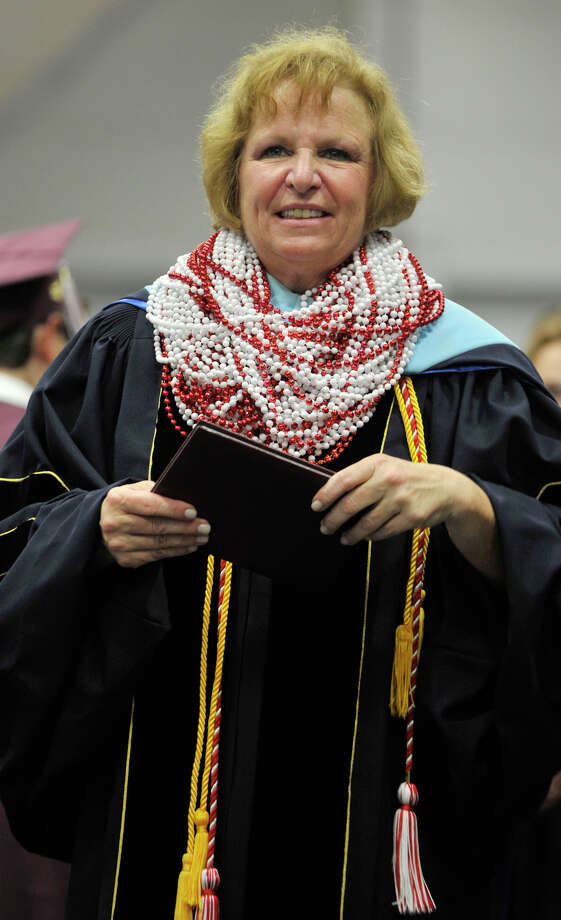 Bethel High School Principal Patricia Cosentino is weighed down by beads that she accepted from every student as they walked across the stage accepting their diplomas during the Bethel High School graduation in the O'Neill Center at Western Connecticut State University's westside campus on Wednesday, June 13, 2012. Photo: Jason Rearick / The News-Times