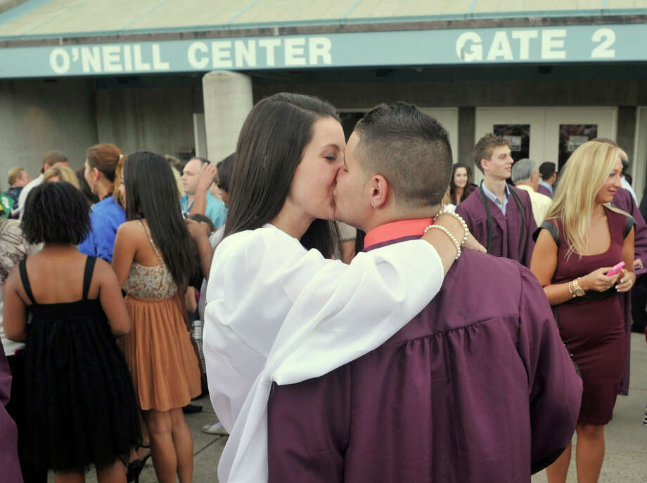 Taylor Lyons, left, and Phil Daluz kiss outside the O'Neill Center after the Bethel High School graduation at Western Connecticut State University's westside campus on Wednesday, June 13, 2012. Photo: Jason Rearick / The News-Times