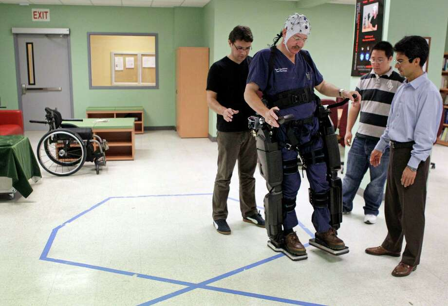 Dr. Eugene Alford, center, who is a paraplegic, tests a robotic exoskeleton surrounded by University of Houston research team members Atilla Kilicarslan, left, and Andrew Paek, and professor Jose Luis Contreras-Vidal, right, in the UH Laboratory for Non-Invasive Brain Machine Interface Systems at the UH Cullen College of Engineering. The robotic exoskeleton is known as Rex, for robotic exoskeleton, and for its manufacturer, New Zealand-based Rex Bionics. Photo: Melissa Phillip, Houston Chronicle / © 2012 Houston Chronicle