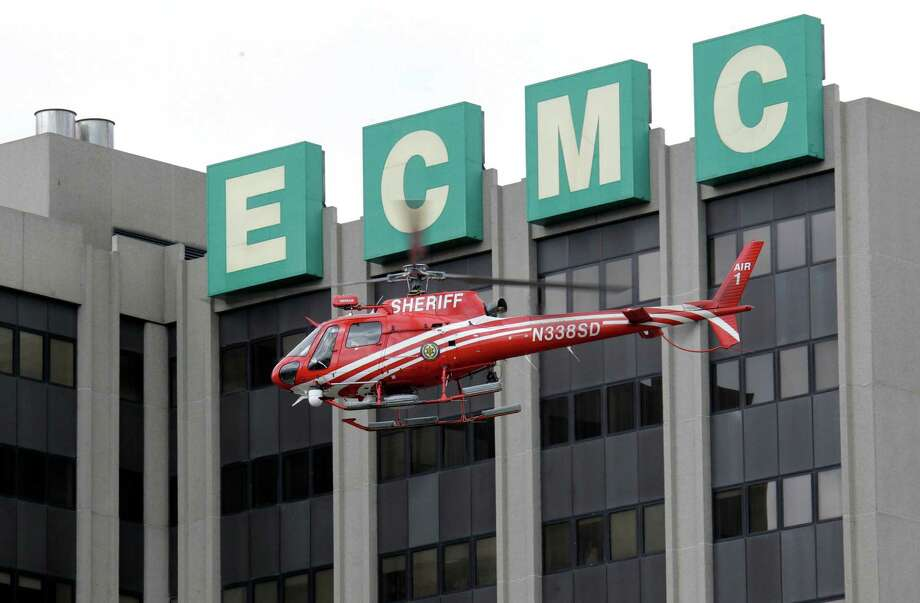 """An Erie County Sheriff's helicopter searches at the scene of a shooting at Erie Count Medical Center in Buffalo, N.Y., Wednesday, June 13, 2012.  A police official confirms that a woman was killed Wednesday morning on the grounds of the Erie County Medical Center, which he describes as being in """"complete lockdown"""" as SWAT teams and other officers cordon off the 65-acre campus. (AP Photo/David Duprey) Photo: David Duprey"""