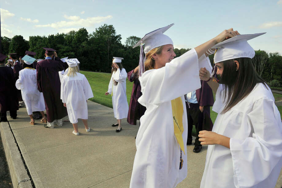 Erin Hannagan, left, helps Stephanie Hirst with her cap before the Bethel High School graduation outside the O'Neill Center at Western Connecticut State University's westside campus on Wednesday, June 13, 2012. Photo: Jason Rearick / The News-Times