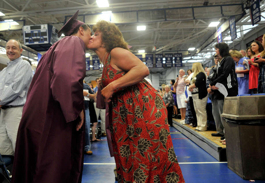Jeanine Quinn, right, kisses the cheek of her son's friend, Brandon Matos, as the class of 2012 files to their seats during the Bethel High School graduation in the O'Neill Center at Western Connecticut State University's westside campus on Wednesday, June 13, 2012. Photo: Jason Rearick / The News-Times