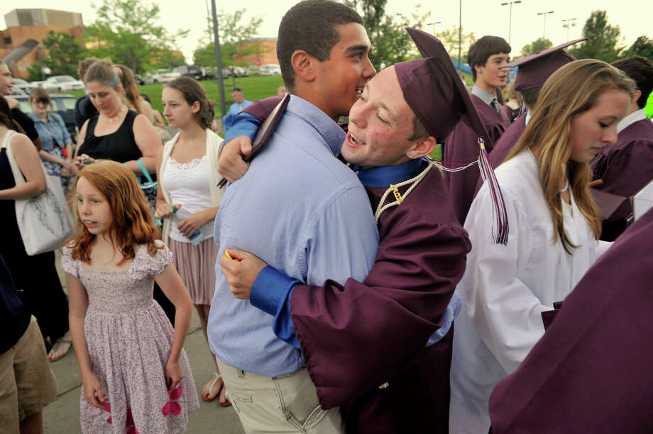 Bethel High 2010 graduate Andre Galvao, left, hugs Ryan Campbell afte the Bethel High School graduation outside the O'Neill Center at Western Connecticut State University's westside campus on Wednesday, June 13, 2012. Photo: Jason Rearick / The News-Times