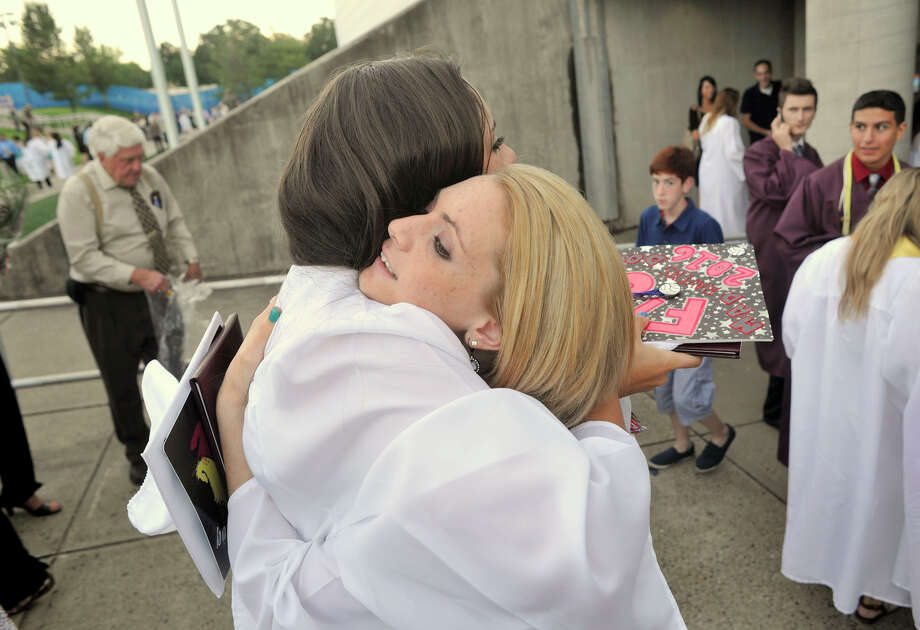 Madison Duffy, left, and Katie Bozzuti hug after the Bethel High School graduation outside the O'Neill Center at Western Connecticut State University's westside campus on Wednesday, June 13, 2012. Photo: Jason Rearick / The News-Times