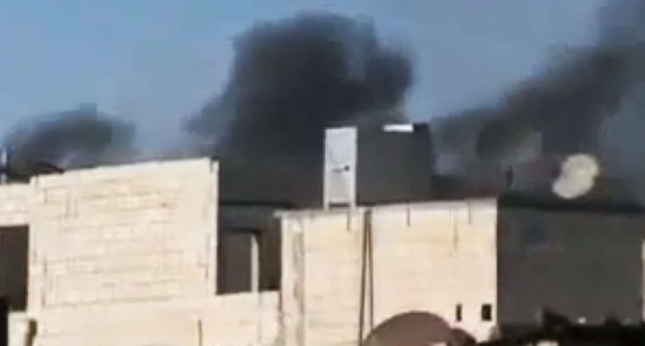 In this image made from amateur video released by the Ugarit News and accessed Wednesday, June 13, 2012, purports to show black smoke rising from buildings in Homs, Syria. Fireballs of orange flames exploded over the central city of Homs, where Syrian forces fired a continuous rain of shells that slammed into the rebel-held neighborhoods of Khaldiyeh, Jouret al-Shayyah and the old city. (AP Photo/Ugarit News via AP video) TV OUT, THE ASSOCIATED PRESS CANNOT INDEPENDENTLY VERIFY THE CONTENT, DATE, LOCATION OR AUTHENTICITY OF THIS MATERIAL Photo: Anonymous