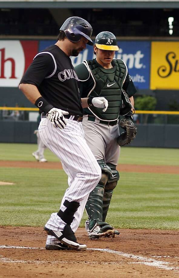 Colorado Rockies' Todd Helton, front, crosses home plate after hitting a grand slam as Oakland Athletics catcher Josh Donaldson looks on in the first inning of a baseball game in Denver, Wednesday, June 13, 2012. (AP Photo/David Zalubowski) Photo: David Zalubowski, Associated Press