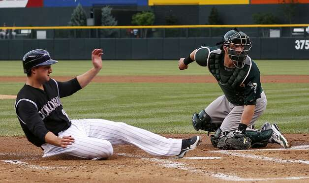 Colorado Rockies' Jordan Pacheco, left, slides safely across home plate to score on a single by Josh Outman as Oakland Athletics catcher Josh Donaldson looks back for the throw from the outfield in the first inning of a baseball game in Denver, Wednesday, June 13, 2012. (AP Photo/David Zalubowski) Photo: David Zalubowski, Associated Press